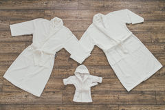 Three white Bathrobe. For family on wooden background Stock Photography
