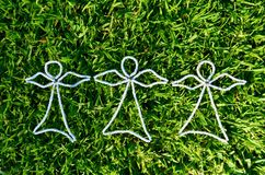 3 white bead angels on freshly mowed green grass background taken from above Royalty Free Stock Photography