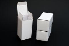 Three white boxes with one opened and the other closed Stock Images