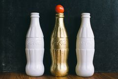 Three White and Brass Coca-cola Bottles Stock Image