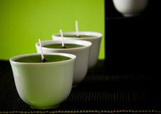 Three white candles on black and yellow Stock Photography