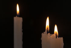 Three White Candles Burning at Night Time. Three white candles burning during the darkness of night time Stock Photography