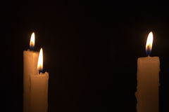 Three White Candles Burning at Night Time. Three white candles burning during the darkness of night time Royalty Free Stock Photo