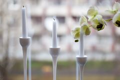 Three white candles in the elegant candle holder with an orchid blossom. Three white candles in the elegant candle holder decorating a table served with an Royalty Free Stock Photography