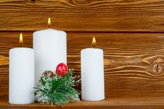 Three white candles with pine brunch Stock Photo