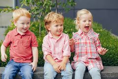 Three white Caucasian cute adorable funny children toddlers sitting together. Group portrait of three white Caucasian cute adorable funny children toddlers stock photo