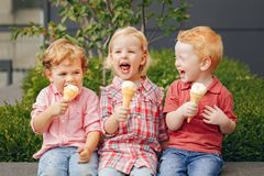 Three white Caucasian cute adorable funny children toddlers sitting together sharing ice-cream food. royalty free stock photo