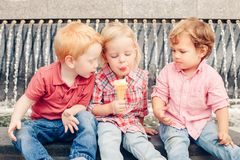 Three white Caucasian cute adorable funny children toddlers sitting together sharing ice-cream food. stock photos