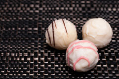 Three white chocolates on dark cloth Stock Photo