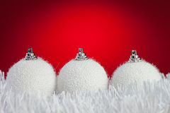 Three white christmas balls on tinsel Stock Photo