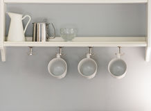 Three white coffee cups hanging in a row. jug and glass sitting Stock Photography