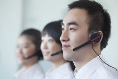 Three White Collar workers in a row with headsets Royalty Free Stock Photos