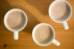 Three white cups of coffee, cocoa or latte on a wooden background on the table, closeup royalty free stock images