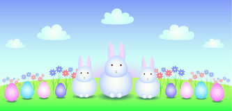 Three white Easter bunny on the field. Three white bunny in the meadow with eggs and flowers Stock Photo