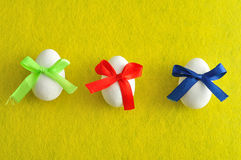 Three white easter eggs with different color bows Stock Image