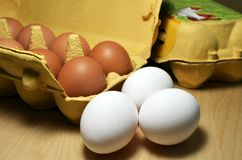 Three white eggs in front of a package with brown eggs. Focus to three white eggs in front of a yellow package with some brown eggs on a wooden table royalty free stock photography