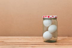 Three white eggs in a glass jar Stock Image