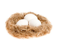 Three white eggs in the nest of straw. On a white background Royalty Free Stock Images