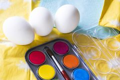 Three white eggs with paint and brush, for Easter royalty free stock image