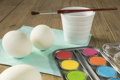 Three white eggs with paint, brush wand water, for Easter royalty free stock photo
