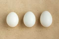 Three white eggs on rustic background with copyspace. Top view of three white eggs on rustic background with copyspace royalty free stock photography