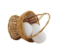 Three white eggs spilled from straw basket Royalty Free Stock Photography