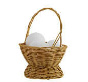 Three white eggs in straw basket isolated Stock Images
