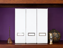 Three white files on a wooden shelf Royalty Free Stock Photo