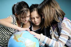 Three white girl studying globe for vacations Royalty Free Stock Photo