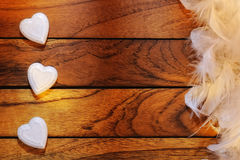 Three white hearts misaligned and feathers. Three white hearts misaligned with wood background and feathers Stock Photography