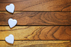 Three white hearts misaligned. With wood background Royalty Free Stock Image
