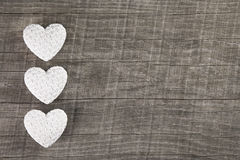 Three white hearts on an old grey brown wooden background. Stock Photography