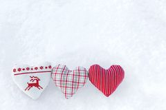 3 Three white hearts with winter cross stitch deer in red on snow. Scandinavian Norwegian styled. Christmas stitching knitting pattern on snowflakes royalty free stock photography