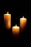 Three White Lighted Candles. Three white candles lit with black background Royalty Free Stock Image