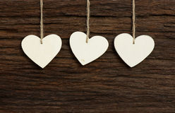 Three White Love Valentine's hearts hanging on wooden texture ba Stock Images