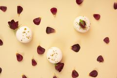 Three white macaroons cakes artfully laid out among the buds and. Petals of dark red burgundy roses on a yellow background. Copy space. Bakery, cooking, gifts Royalty Free Stock Images