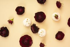 Three white macaroons cakes artfully laid out among the buds of. Dark red burgundy roses on a yellow background. Copy space. Bakery, cooking, gifts, conceptual Stock Photo
