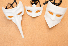 Three white masks on cork wooden background Royalty Free Stock Photos