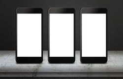Three white mobile phones on table with blank, white, isolated display screen for mockup Royalty Free Stock Images