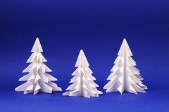 Three white paper trees on blue background Origami trees. Horizontal Stock Photography