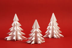 Three white paper trees on red background Royalty Free Stock Photo