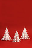 Three white paper trees on red background - vertical Stock Photos