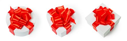 Three white pasteboard square gift boxes. With red satin bow and ribbon isolated on white background with clipping path. Square, round and heart shape Royalty Free Stock Photography