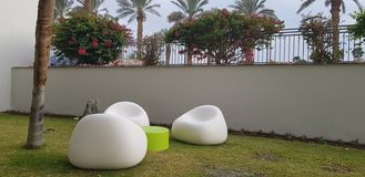 Three white plastic chairs stay empty round a small table on the grass stock photo