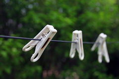 Three white plastic simple normal clothespins on a black rope on Royalty Free Stock Image