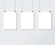 Three white poster on brick wall Royalty Free Stock Images