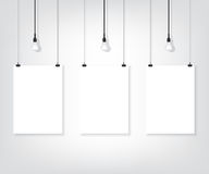 Three white poster on wall and bulb Royalty Free Stock Photography