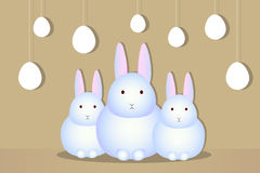 Three white rabbit silhouettes eggs. Three young white bunny on a beige background, silhouettes eggs on strings Royalty Free Stock Photography