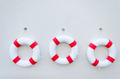 A three White red Lifebuoy with a board on white wall Royalty Free Stock Photos