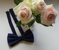 Three white roses and bow tie. White background. ! royalty free stock images